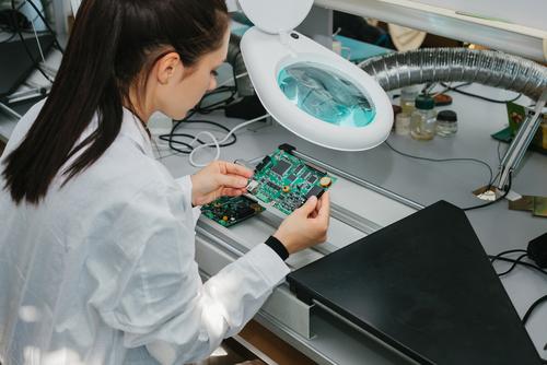 Une jeune ingénieure systèmes embarqués qui teste une carte électronique