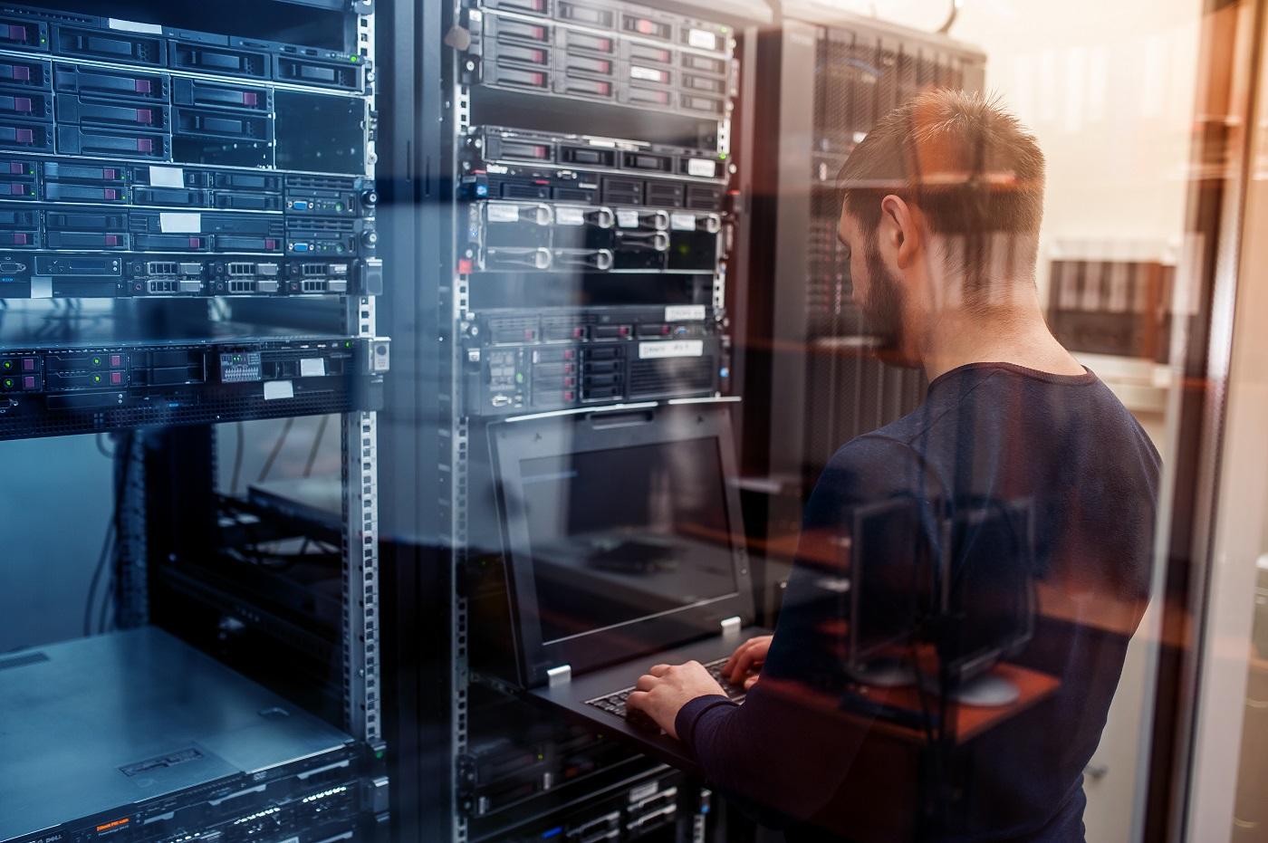 Un jeune ingénieur en télécommunications qui examine un serveur