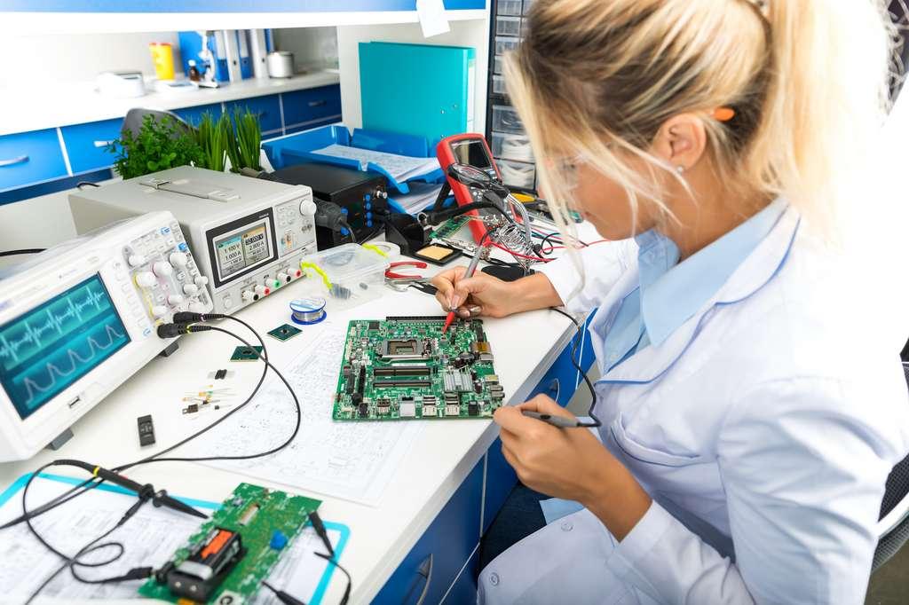 Une jeune ingénieure en informatique industrielle qui vérifie une carte électronique